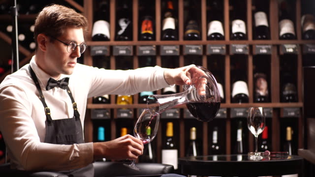 skilled sommelier pouring wine from decanter ino wine glass - decanter video stock e b–roll