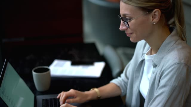 Skilled woman keyboarding email message using application on laptop computer connected to internet