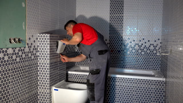 skilled worker man install toilet flush button in new modern bathroom
