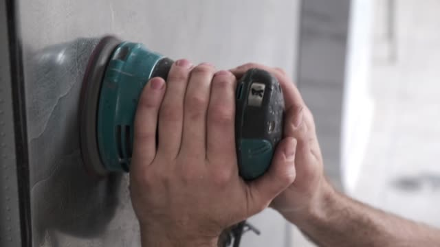 Skilled worker man polishes plastered wall with an electric hand sanding machine. Master making repair in a office.