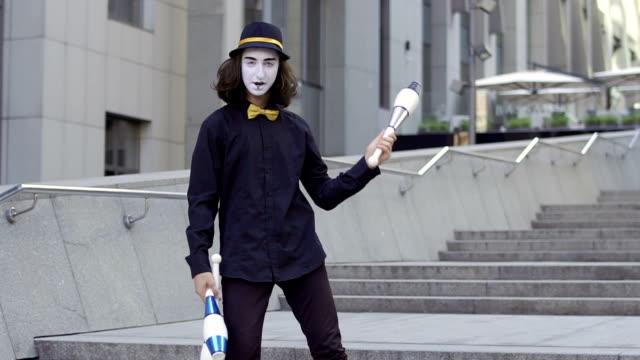 skillful mime juggling pins standing at staircase near office center - гримировальные краски стоковые видео и кадры b-roll