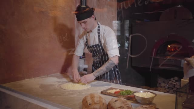 Skillful pizza maker is cooking dough at modern restaurant