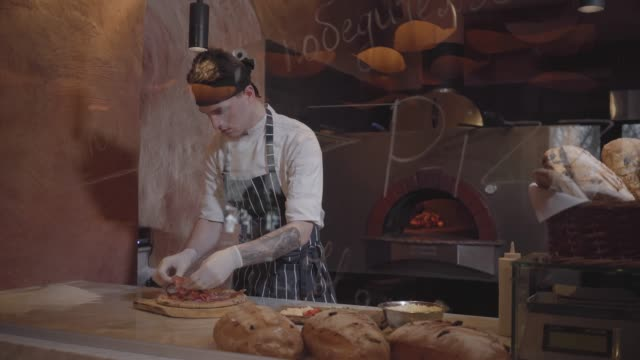 Skillful pizza maker is cooking pizza at modern restaurant kitchen behind glass.