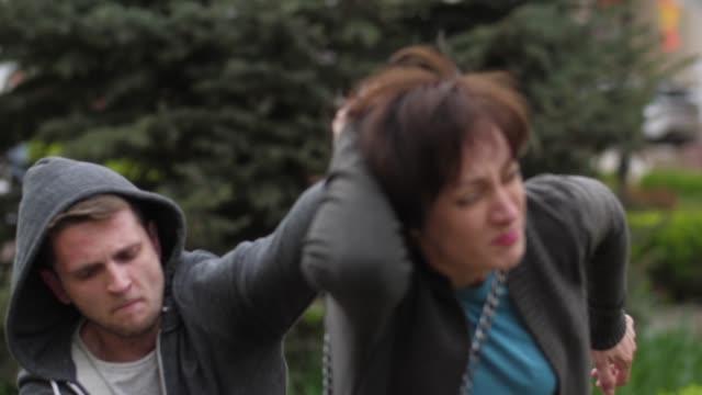vídeos de stock e filmes b-roll de skillful woman preventing theft attempt in park - roubar crime