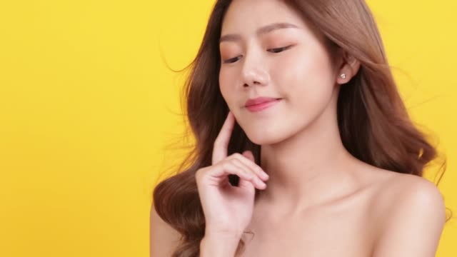 skin care concept. portrait posing asia beauty woman hand touch face and shoulder with yellow background studio shooting