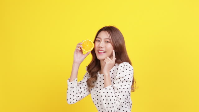 skin care concept. portrait posing asia beauty woman hand touch face and shoulder with yellow background studio shooting.asia female smile happyness holding fresh orange slide