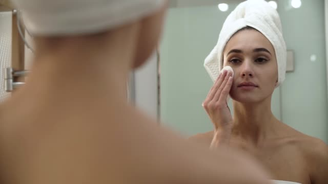 skin care. woman cleaning face with lotion at bathroom - viziarsi video stock e b–roll