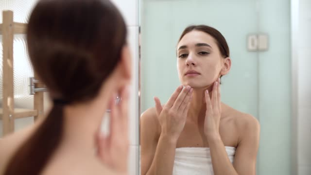 skin care. woman touching face and looking at mirror at bathroom - viziarsi video stock e b–roll
