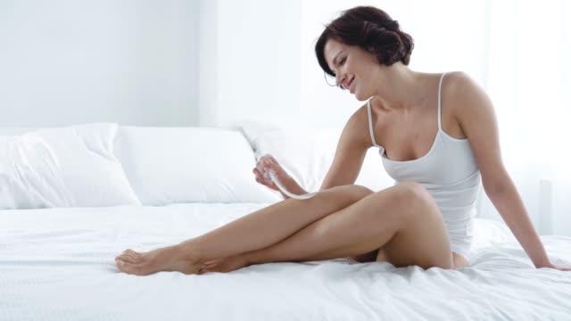 skin care. woman touching leg with feather sitting on bed - depilacja filmów i materiałów b-roll