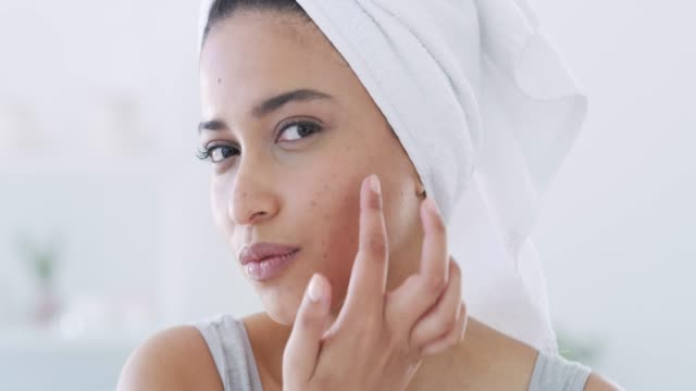 Skincare is important to me 4k video footage of a beautiful young woman applying moisturizer to her skin in the bathroom at home body care stock videos & royalty-free footage