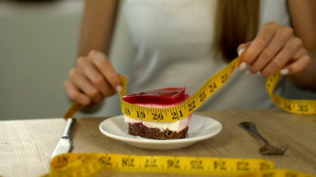skinny girl measuring piece of cake with tape-line, calculating calorie intake - proibizione video stock e b–roll