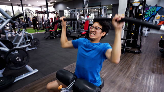 skinny man try hard and fail at gym, wide-grip lat pulldown - strength training stock videos & royalty-free footage