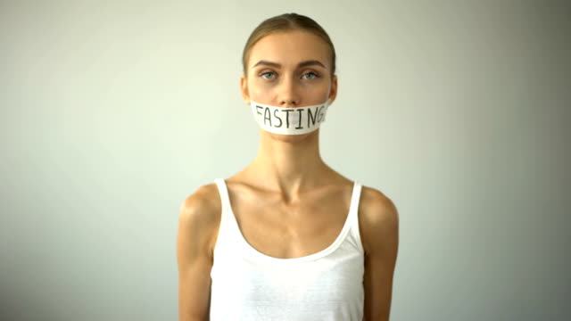 тощая женщина с лентой рот показывает пустую тарелку, концепция поста, голода - поститься стоковые видео и кадры b-roll
