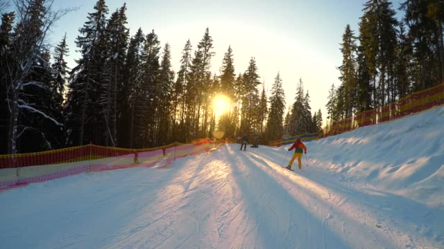 skis down sunny groomed slope skiers in the mountains - utah video stock e b–roll
