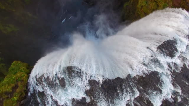 AERIAL Skogafoss waterfall Aerial shots of the spectacular Skogafoss waterfall with a small village in the distance. Iceland. Time Warp effect. Also available in 4K resolution. rapids river stock videos & royalty-free footage