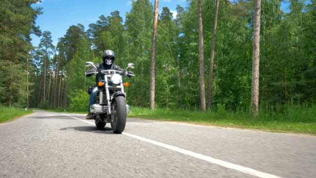 a skull face motorcyclist rides on a sunny road. - bike tire tracks video stock e b–roll