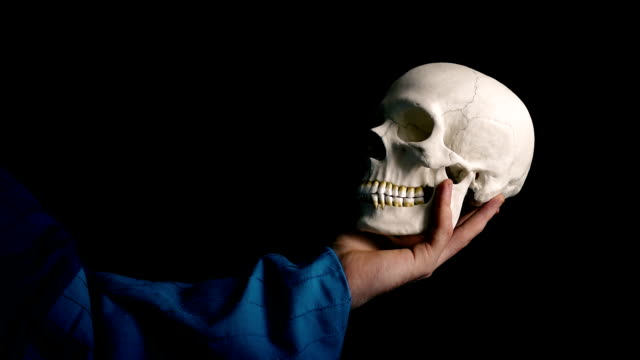 Skull Held Out - Theater Acting Concept 2 Versions - Actor holds out skull against black background skull stock videos & royalty-free footage
