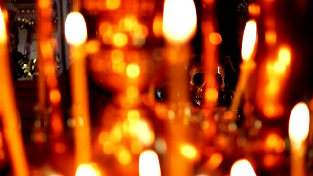 Skull in focus, in the foreground burning candles in the Christian Orthodox Church video
