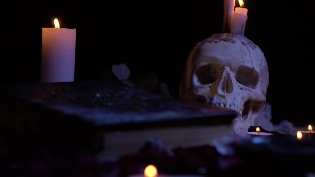 Schädel mit Kerzen und einem alten Buch auf dem Tisch, Schieberegler schießen – Video