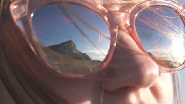 Sky and mountains are reflected in the glasses of a young girl video