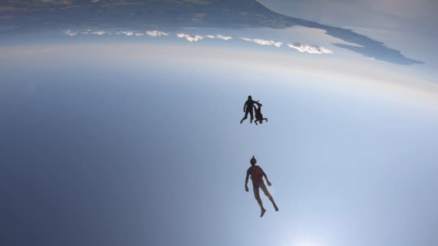 Sky divers in free fall above city and green fields