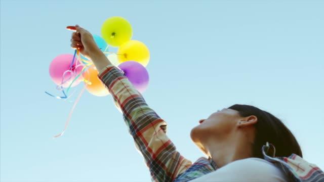 vídeos de stock e filmes b-roll de sky is the limit. - mulher balões