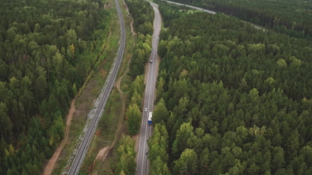 Sky view of summer road with cars and trucks. Summer forest and highway road drone view. Aerial landscape. Tracking shot.