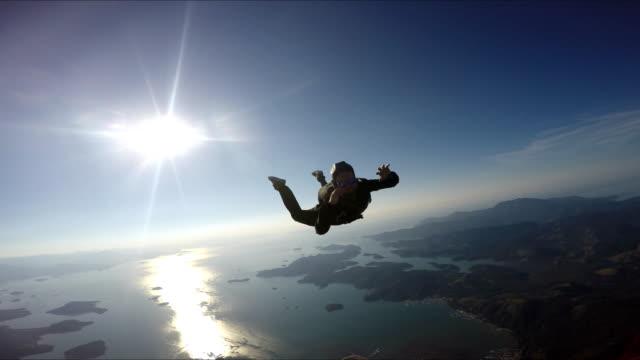 skydiver having fun above the sea & mountains 4k - скайдайвинг стоковые видео и кадры b-roll