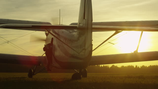 skydiver is getting in propeller airplane in sunset light - скайдайвинг стоковые видео и кадры b-roll