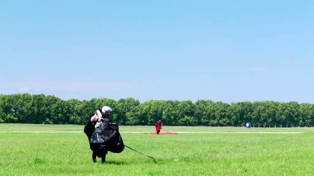 Skydiver lands on the field and collects a parachute. Airdrome for training skydiving. Skydiver lands on the field and collects a parachute. landing touching down stock videos & royalty-free footage