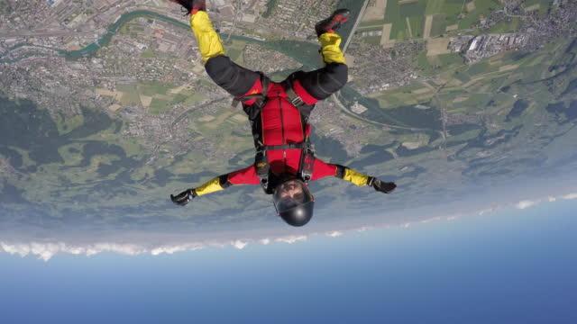 vídeos de stock, filmes e b-roll de para-quedista executar movimentos acrobáticos em queda livre - paraquedismo