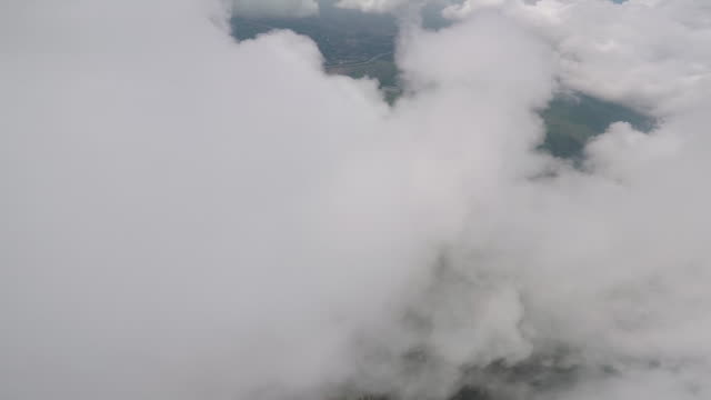 skydiver perspective of descending through lofty clouds - бейсджампинг стоковые видео и кадры b-roll