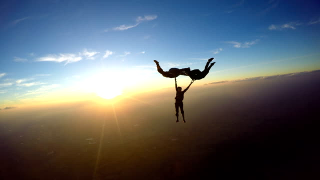 skydivers having at the amazing sunset 4k video - adrenalina video stock e b–roll