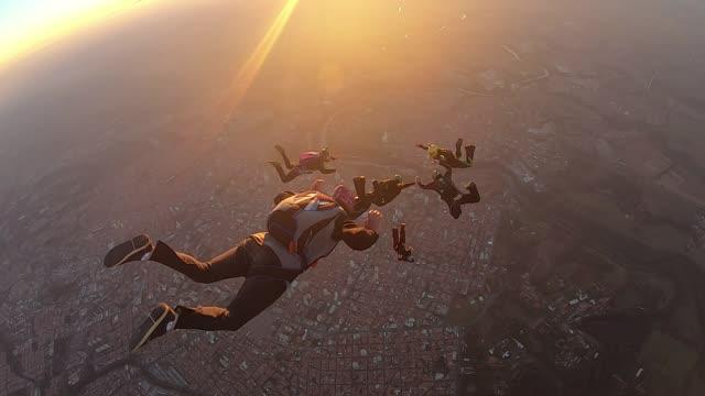 vídeos de stock, filmes e b-roll de os pára-quedistas saltam no por do sol impressionante - paraquedismo