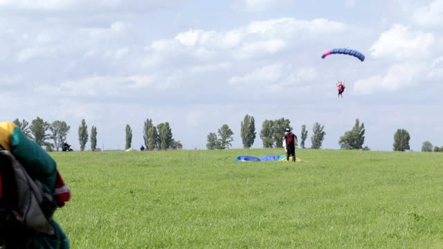 Skydivers land on the field. An elderly skydiver carries his parachute. Airdrome for training skydiving. Skydivers land on the field. An elderly skydiver carries his parachute. landing touching down stock videos & royalty-free footage