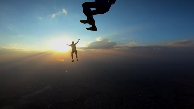 Skydivers making a sit fly position at the sunset