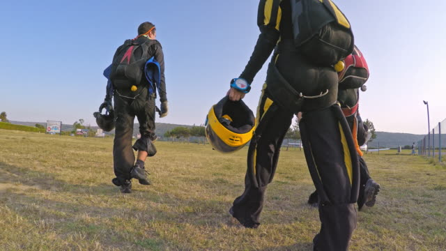 Skydivers walking across the airport field video