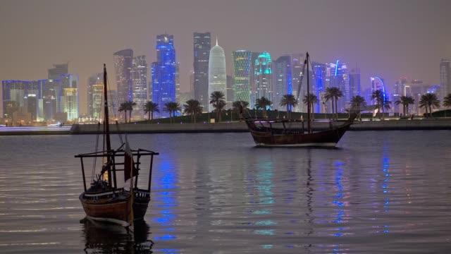 vidéos et rushes de skyline de doha, qatar avec des bateaux dhow arabes traditionnels la nuit. - doha