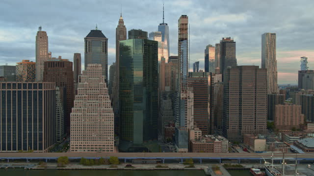 Skyline of Downtown Manhattan includes Freedom Tower, waterfront, FDR Drive, and East River Esplanade. The view from East River at sunrise. Aerial video with the cinematic panning camera motion.