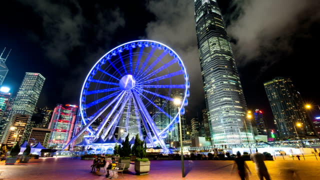 Skyline,ferry wheel,tourists and modern buildings in hong kong at night,hyper lapse. video