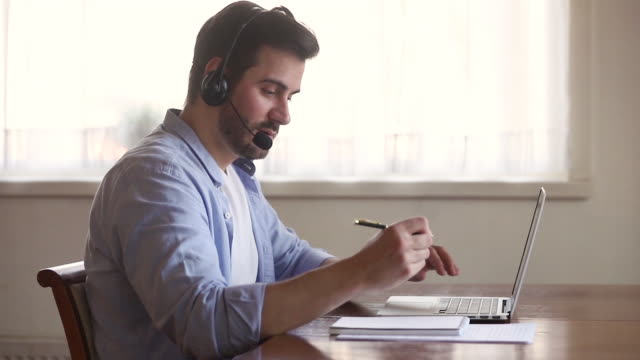 skype teacher wearing headset looking at laptop screen making notes - conference call stock videos & royalty-free footage