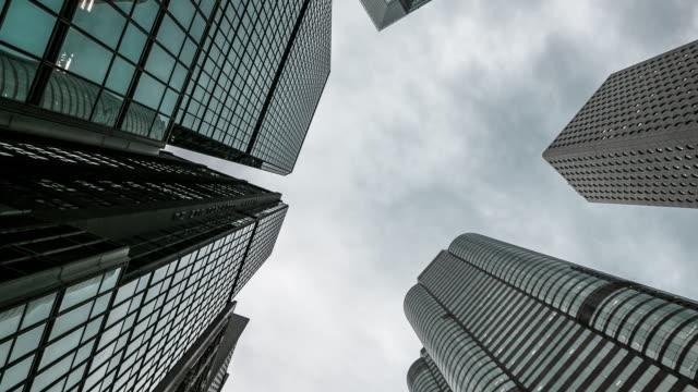 vidéos et rushes de gratte-ciel entassés des immeubles de grande hauteur avec le ciel et les nuages au-dessus de la tour, time lapse - vue en contre plongée