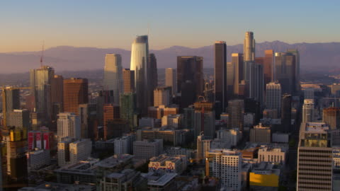 AERIAL Skyscrapers in Downtown Los Angeles at sunset Aerial shot of the business buildings in Downtown Los Angeles at sunset. Shot in CA, USA. usa stock videos & royalty-free footage
