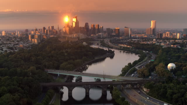 aerial skyscrapers of center city in philadelphia reflecting the rising sun - восход солнца стоковые видео и кадры b-roll