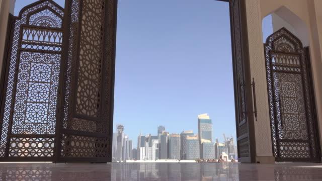 vidéos et rushes de gratte-ciels de doha par la porte ajourée de la mosquée - doha