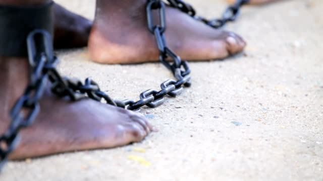 Slaves feet shackled together Slaves feet shackled together as they walk along slowly.  human trafficking stock videos & royalty-free footage
