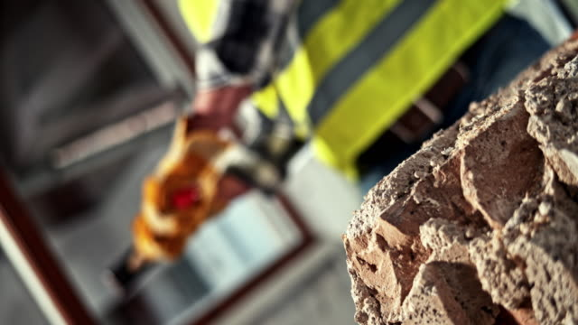 SLO MO LD Sledge hammer being used to break up masonry