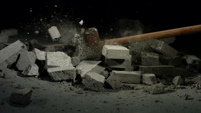 Sledge hammer hitting concrete bricks video