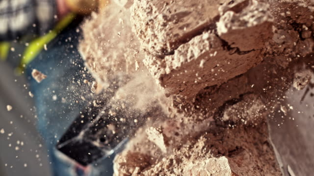 SLO MO Sledge hammer striking a brick wall Slow motion close up handheld shot of a sledge hammer striking a brick wall and breaking it up. Shot in Slovenia. breaking stock videos & royalty-free footage