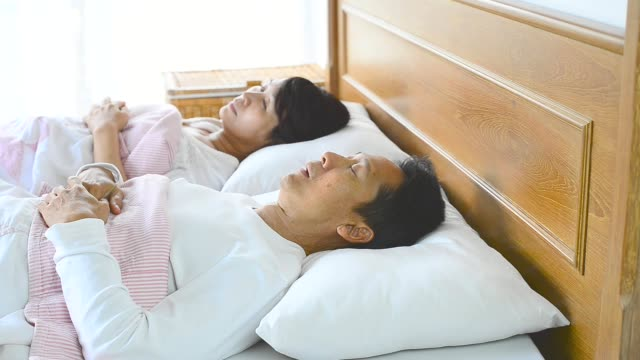 Sleep apnea man snoring and choking loud ,waking his wife up during the night, closing ears with pillow . video
